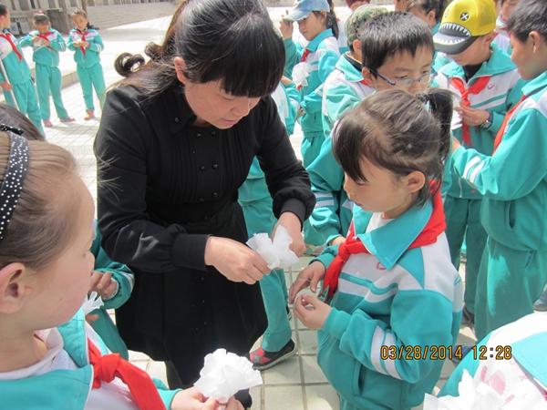 图为西宁市观门街小学校长亲自带领学生们制作小白花.