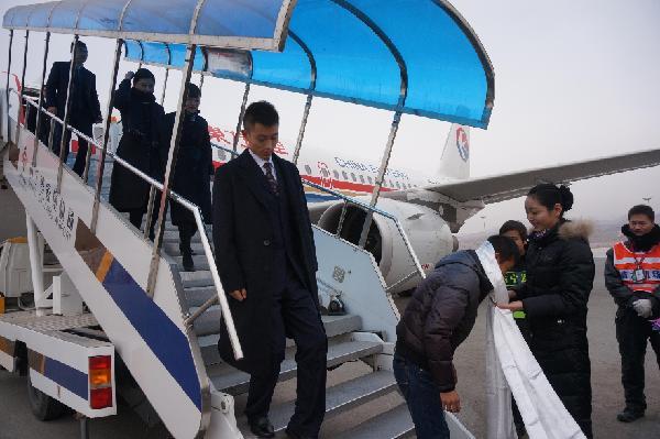 航班降落在西宁曹家堡机场,机组人员陆续走下飞机,工作人员为第400万