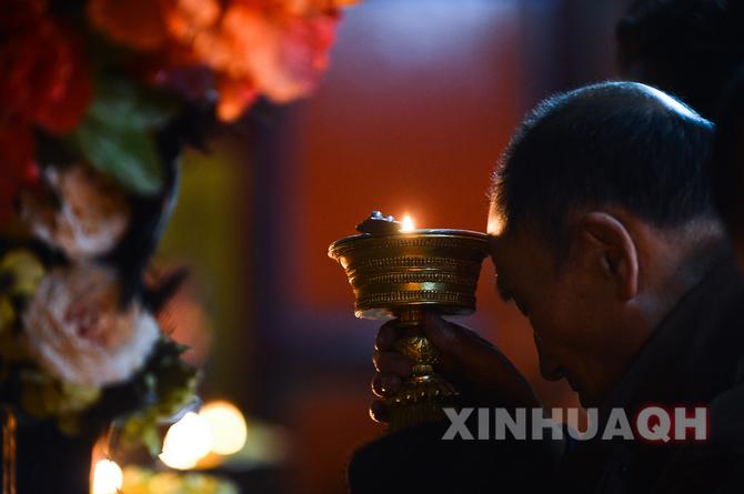 一名信徒在青海塔尔寺燃灯祈福