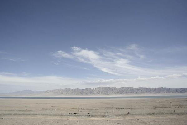 柴达木盆地是我国内陆大型的山间盆地,盐类沉积储量居世界之冠,是一个盐的世界,有聚宝盆的美誉。柴达木在蒙语中的意思是盐泽,这个名字非常确切地表达出了柴达木盆地的自然景观,盆地内有湖泊51个,其中淡水湖1个(克鲁克湖),半咸水-咸水湖7个,盐湖43个。 柴达木盆地居于青藏高原的东北侧,位于东经9000-9820,北纬3555-3910之间,四周为高大山系所围绕,构成了一个轴向为北西-南东向的不规则的菱形向心汇水盆地,盆地长轴约为65