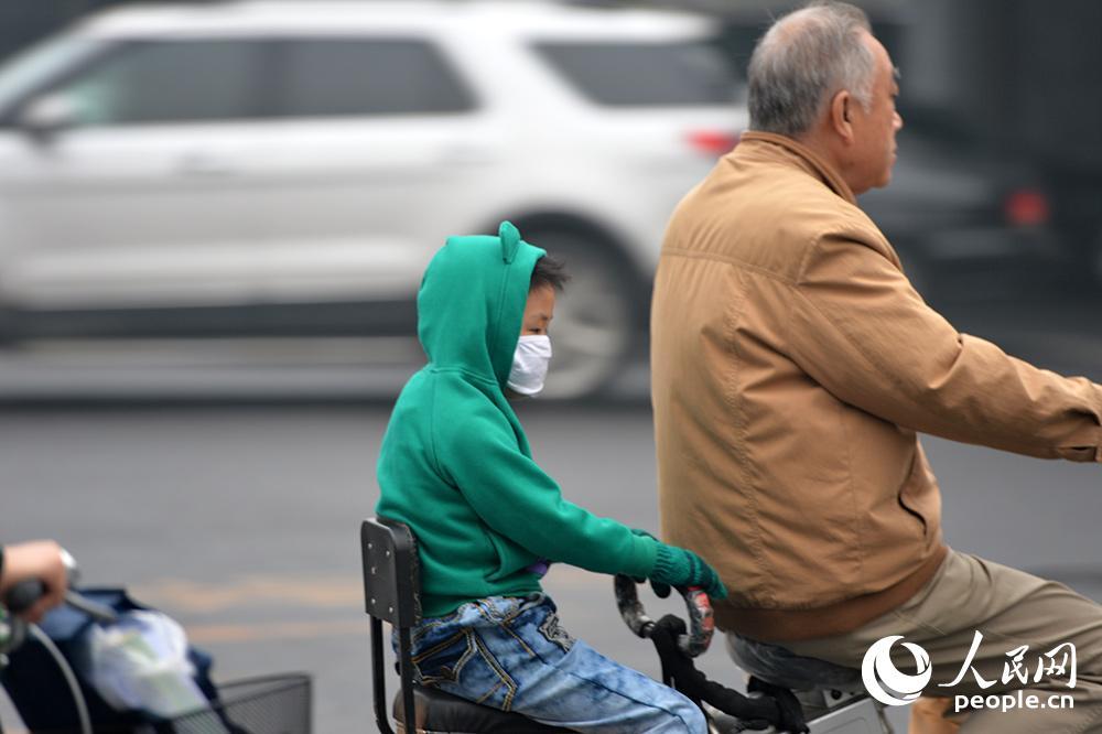 人民网北京10月10日电(记者翁奇羽)10月10日,受雾霾持续影响,北京市区能见度低,市民纷纷戴口罩抵御雾霾。当日,由于受静稳天气及较好的湿度条件影响,北京、天津、华北、黄淮等地的部分地区持续雾霾天气,中央气象台06时继续发布霾橙色预警及大雾黄色预警。