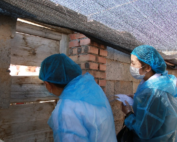 防疫人員隔著門縫量體溫
